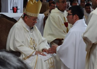 Diego Gallardo, C.PP.S., kneels before Archbishop and Monsignor Rene Rebolledo during the ordination.