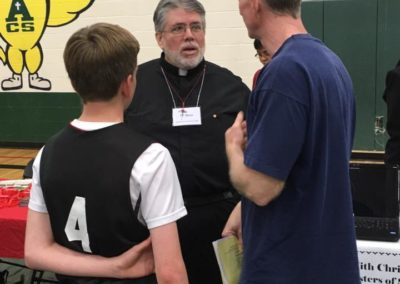 Fr. Steve Dos Santos, C.PP.S., talks with parents and students at a vocation event.