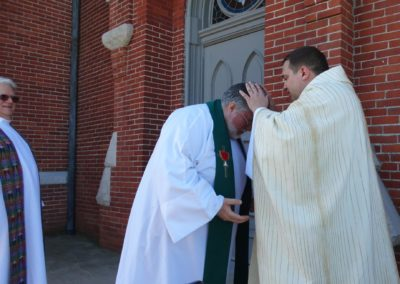 Fr. Jim Smith, C.PP.S., gives a blessing to Fr. Steve Dos Santos Cpps, as Fr. Dennis Chriszt, C.PP.S., looks on.