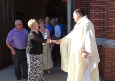 Fr. Jim Smith, C.PP.S., greets Pat Stachler after Mass at St. Henry.