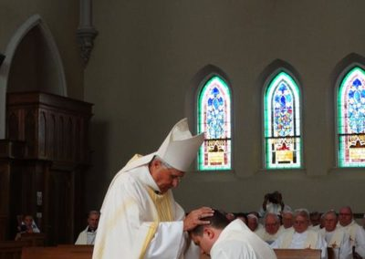 Bishop Charron lays hands on James Smith during the ordination rite.