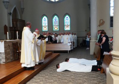 Bishop Joseph Charron, C.PP.S., offers a prayer at the end of the litany of saints, over James Smith and Matthew Keller. Deacon Randy Balster of the St. Henry, Ohio, Cluster is at left and Matt's family is at right.