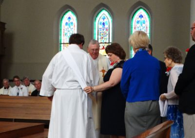 Matthew Keller's mother, Carol, and Fr. Ken Schroeder, C.PP.S., place the deacon's stole on Matt as his family members look on.