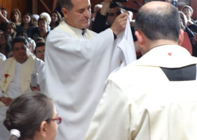 Fr. Antonio Baus, C.PP.S., assists Diego with the vestments.