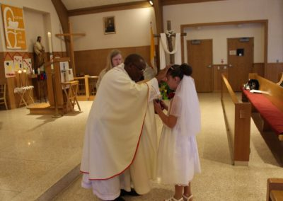 Fr. Alfons Minja, C.PP.S., offers a blessing on first communicants at Our Lady of Guadalupe, Montezuma, Ohio.