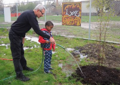 Fr. Denny Kinderman, C.PP.S., and a young helper water flowers at PBMR.