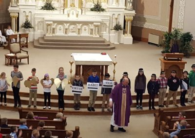 Fr. Ken Schnipke, C.PP.S., preaches about virtue during the Immaculate Conception school Mass.