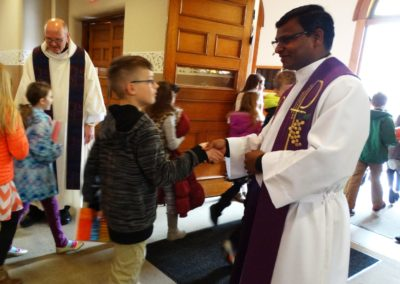 Fr. Jayababu Nuthulapati, C.PP.S., greets students after the school Mass Friday at Immaculate Conception in Celina, Ohio. The pastor, Fr. Ken Schnipke, C.PP.S., is to the left.