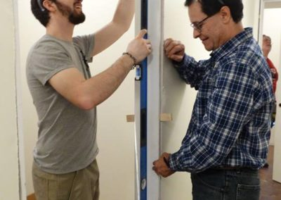 Luis Montoya, right, works with a carpenter to install a door jamb.