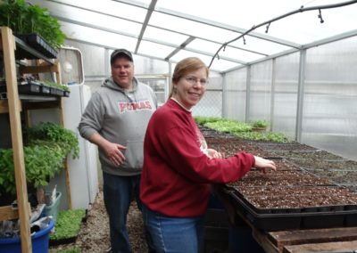Tom Doorley and Colleen Kammer plant seeds in the farm's greenhouse.