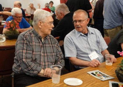 Frs. Vince Hoying and Tom Hemm talk at Monday's social.