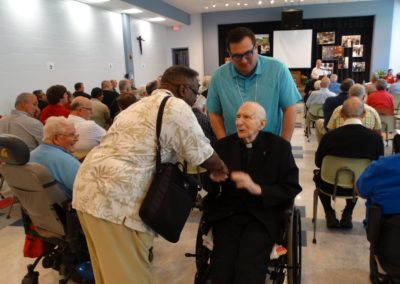 Fr. Clarence Williams, C.PP.S., greets Fr. Len Kostka, C.PP.S., after Fr. Kostka, 104, delivered his message to the assembly. Fr. Jim Smith, C.PP.S., assists.