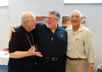 Newly elected councilor Fr. Steve Dos Santos is congratulated by C.PP.S. Frs. Charles Mullen, left, and Jerry Steinbrunner.