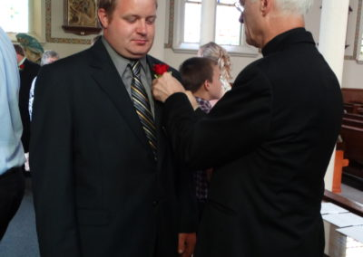 Before the ordination Mass, Fr. Angelo Anthony, C.PP.S., right, pins a boutonniere on Matt's brother, Scott.