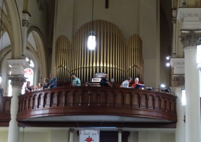 Musicians in the choir loft at St. John the Baptist prepare before Mass.