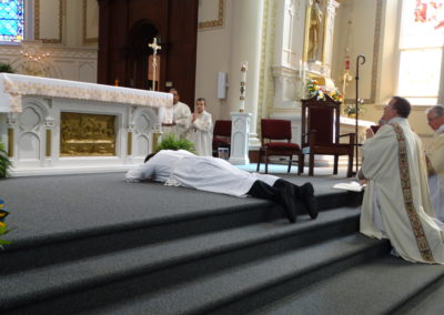 Matthew Keller lays prostrate during the litany of the saints.