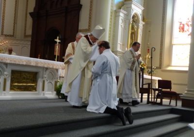 The bishop lays his hands on Matthew Keller.