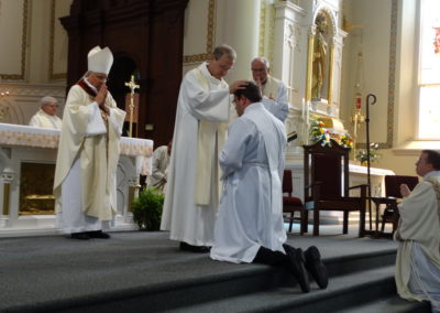 Fr. Larry J Hemmelgarn, C.PP.S., provincial director, lays hands on Matthew Keller.
