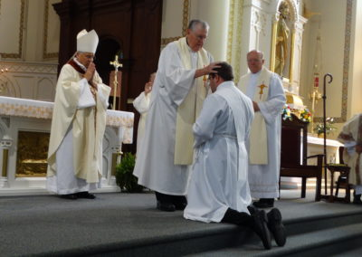 Fr. Ken Schroeder, C.PP.S., Matt's former pastor, lays hands on him as he is ordained.