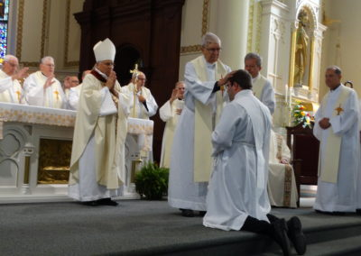 Fr. Jim Dugal, C.PP.S., lays hands on Matthew Keller.