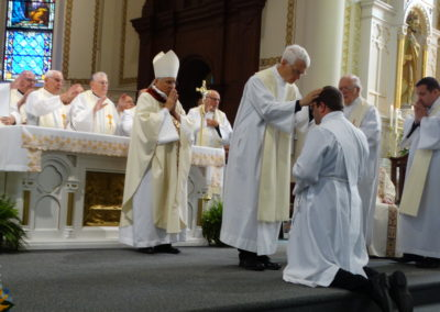Fr. Angelo Anthony, C.PP.S., lays hands on Matthew Keller.