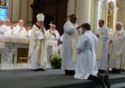Fr. Alfons Mopia Minja, C.PP.S., lays hands on Matthew Keller.