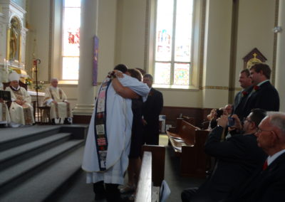 Fr. Matt embraces his mom, Carol, as his father, Paul, and brothers look on.