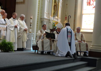 The bishop anoints Fr. Matt's hands with chrism oil.