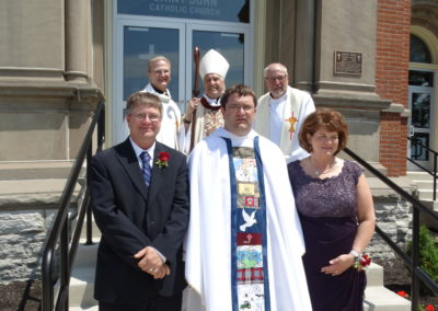 Fr. Matthew Keller with his parents, Paul and Carol Keller, and Fr. Larry J Hemmelgarn, Bishop Joseph Charron and Fr. Bill Nordenbrock.