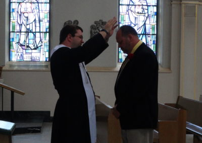 Fr. Matthew Keller offers a first blessing to his godfather, James Ahrns.