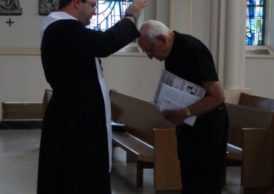 Fr. Matthew Keller offers a first blessing to Fr. Paul Wohlwend, C.PP.S.
