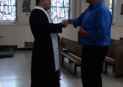Fr. Matthew Keller offers a first blessing to Greg Evers.