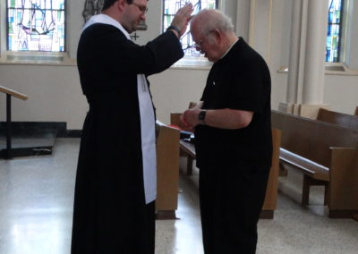 Fr. Matthew Keller offers a first blessing to Fr. Charles Mullen, C.PP.S.